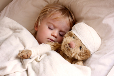 Sleeping boy with bandaged teddy bear