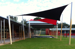 Rainbow shade sail fabric in black and red sails in a school.
